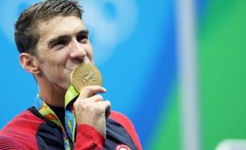 Michael Phelps besando una medalla de oro