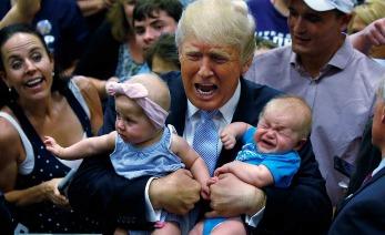 Donald Trump cargando a dos bebes