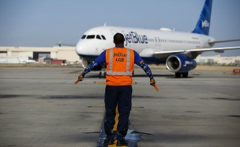 An aircraft marshaller guides a JetBlue Airways Corp. Airbus Group SE A320 aircraft on the tarmac at Long Beach Airport (LGB) in Long Beach, California, U.S., on Monday, April 25, 2016. JetBlue Airways Corp. is scheduled to release earnings figures on April 26. Photographer: Patrick T. Fallon/Bloomberg