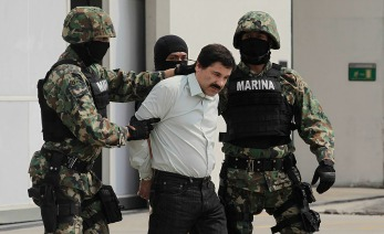 """MEXICO CITY, MEXICO - FEBRUARY 22:  Joaquin """"El Chapo"""" Guzman is escorted to a helicopter in handcuffs by Mexican navy marines at a navy hanger. Guzman leader of Mexico's Sinaloa drug Cartel, was captured alive overnight in the beach resort town of Mazatlan, considered the Mexican most-wanted drug dealer on February 22, 2014 in Mexico City, Mexico. (Photo by STR/LatinContent/Getty Images)"""