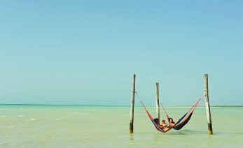 Mexico, Quintana Roo, Isla Holbox, couple with baby in a hamac in the wind in green turquoise sea