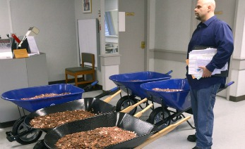 Nick Stafford waits for his number to be called as he stands beside of 5 wheelbarrows full of change, mostly pennies, at the DMV in Lebanon, Virginia. Stafford was paying the sales tax on two cars that he was titling. (AP Photo, DAVID CRIGGER/Bristol Herald Courier)