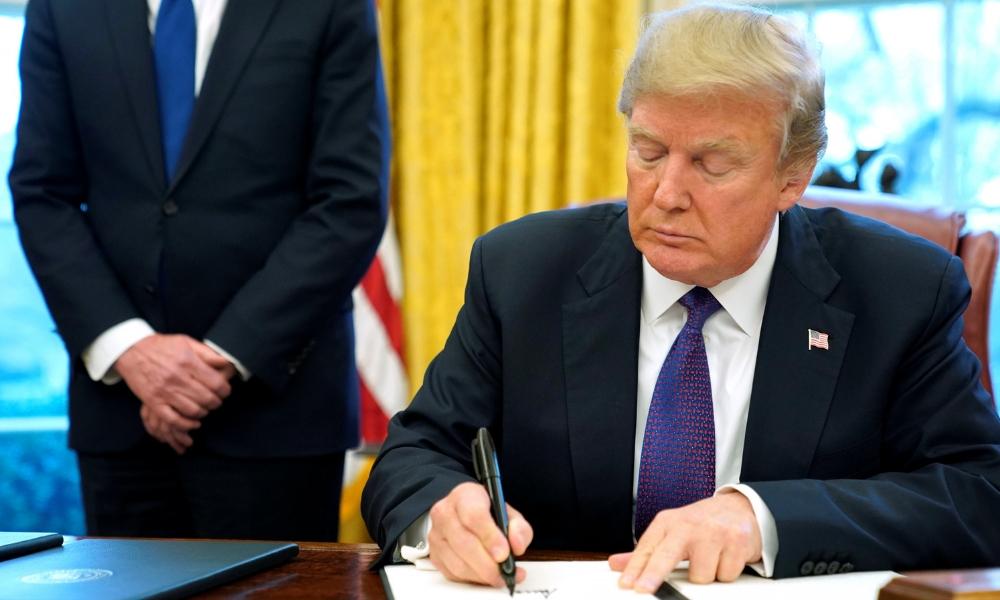 Donald Trump firma con marcadores negros